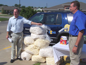 Monte Shaw and Craig Floss stand near pile of popcorn