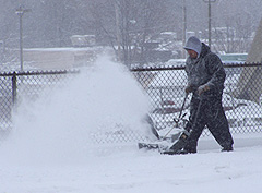 Man uses snowblower to clear a sidewalk in Des Moines