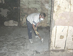 A volunteer chips away flood damaged tile in a Cedar Rapids church.