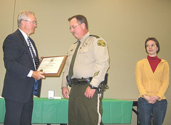 Deputy Perry Ghee receives award from Sheriff Dennis Anderson as Sarah Elrod looks on.