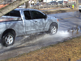 A truck drives through standing water in Des Moines caused by melting snow.