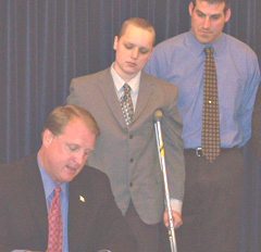 Governor Chet Culver signs bill as Drew Wall, Nick Ackerman watch.