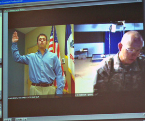 Lieutenant Colonel Hal Turner  (left) swears his son Brett into the military via the internet.