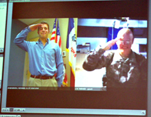 Brett Turner (right) in Johnston and Hal Turner in Iraq salute each other via internet webcams.