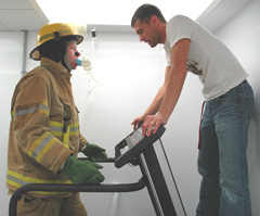 I.S.U. kinesiology research associate Hector Angus explains the physical testing procedures to firefighter Mike Hartman, captain of the Muscatine Fire Department.