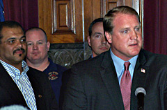 Representative Kerry Burt (far left)  listens to Governor Culver during an event at the capitol earlier this year.