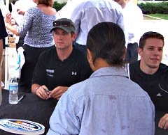 Brad Keselowski (right) signs autographs with Miahcael Annett  at an event in Des Moines.