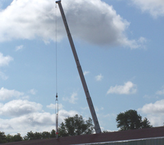 A crane lifts the 40 foot periscope into place.