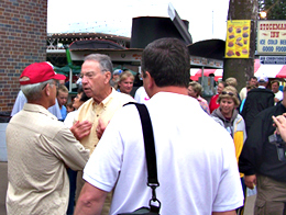 Iowa Senator Chuck Grassley (yellow shirt) talks with people outside the cattle barn at the Iowa State Fair.