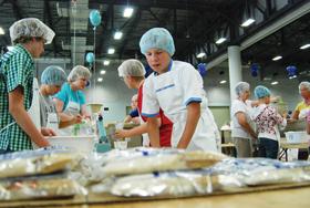 Volunteers package meals.