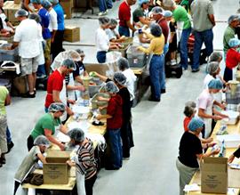 Volunteers pack meals.