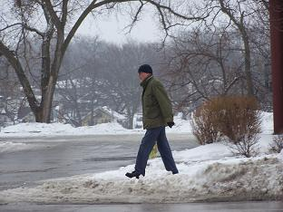 Man carrying bag of ice melt in Des Moines