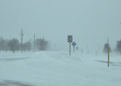 Snowfall piled up and blowing along the roadway.