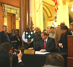 Governor Culver signs reorganization bill as Democratic lawmakers surround him in the statehouse rotunda.