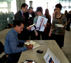 Mitt Romney signs his book.