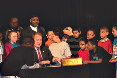 Governor Culver signs the bill as school kids and Representative Ako Abdul-Samad look on.