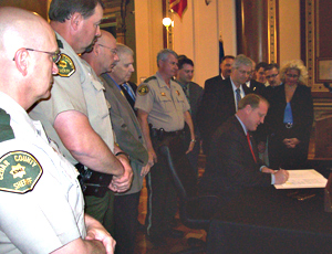 Govenror Culver signs the gun bill as law officers look on.
