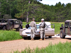 Soldiers check out a car used to simulate an explosion during a traing exercise.