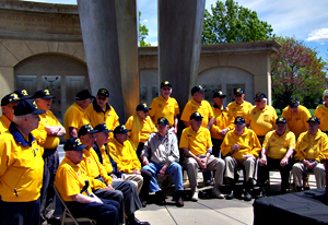 Veterans wearing yellow shirts and black hats.