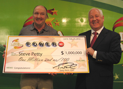 Lottery winner Steve Petty holds check presented by Iowa Lottery C.E.O. Terry Rich.