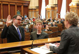State Representative Todd Prichard  takes the oath of office in the Iowa House of  Representatives.  His wife, Ann, is holding the bible.