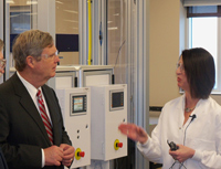 Ag Secretary Tom Vilsack talks with senior research director Hillary Sullivan during a tour of the Dupont-Pioneer research facility.
