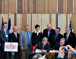 Ag Secretary Tom Vilsack signs agreement with Dupont VP Jim Borel.
