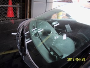 Winshield bullet holes visible in from outside the car.