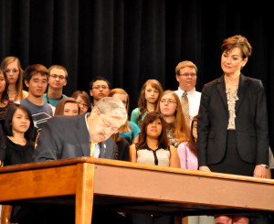 Governor Branstad signs the bill as students look on.