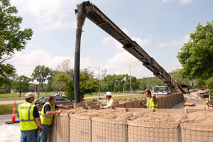 Workers filling HESCO barriers at University of Iowa in May. (U-I photo)