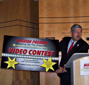 Governor Branstad holds a poster for the video context.