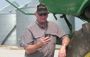 Joe Hossel checks on his farm via his phone.