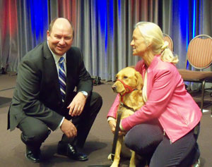 Hy-Vee CEO Randy Edeker with Puppy Jake and Becky Beach, president of the Puppy Jake Foundation.