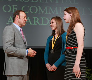 Actor Kevin Spacey congratulates Katelyn Cinnamon, 18, of West Des Moines (center) and Samantha Dilocker, 13, of Red Oak (right) on being named Iowa's top two youth volunteers for 2013.