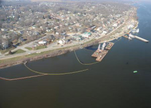 Booms and barges surround a sunken towboat near Le Claire.