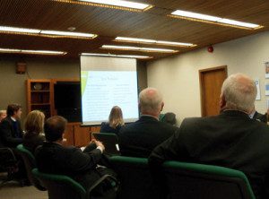 Iowa Lottery Board members watch a presentation on the proposed new building.
