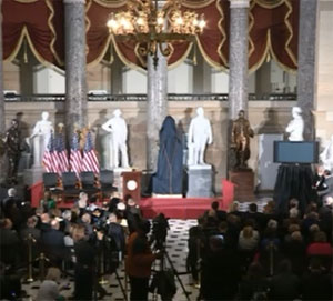 The Borlaug statue draped in a blue cover prior to the unveiling.