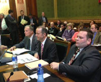DAS director Mike Carroll, (center) flanked by two top aides testifies before lawmakers.