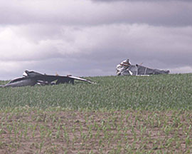 Grain bins blown into a field.