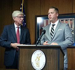 Staff Sergeant James Wilson (podium) with Attorney General Tom Miller.