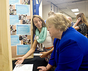 Student Lily Fuger (left) explains to Nancy Grove how she detects levels of BPA in plastics.