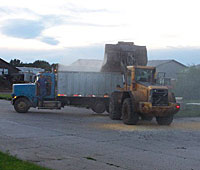 A loader dumps grain from a coop fire in Sioux Center.