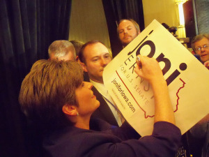 Ernst signs a campaign sign for a supporter.