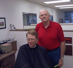 Kyle Peterson gets his hair cut by retiring barber Neil Peck.