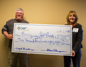 The Superintendent of Montezuma Municipal Light and Power, Kevin Kudart, receives a check.