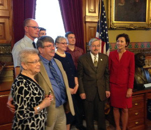 Judy Harberts, to Branstad's immediate  left, poses for a family photo with Branstad after bill signing. Rep. Dean Fisher of Garwin, the bill's floor manager, stands on Harberts' right.