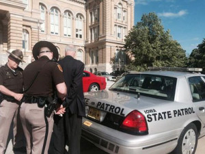 Former legislator Ed Fallon being escorted from the state capitol.