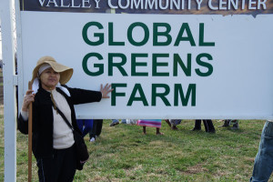Ta Kaw Pa from Burma shows off the Global Greens Farm sign.