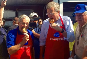 "Jeb Bush and Terry Branstad eating ""pork on a stick."""