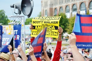 Protestors hold up yellow signs during Scott Walker's speech at the Soap Box